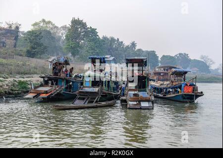 Boats docked alongside the Irrawaddy River near Mandalay Myanmar - Stock Image
