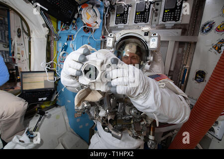 NASA astronaut Nick Hague is fitted in a U.S. spacesuit and checks out a spacewalk camera before his first spacewalk in the Quest Airlock March 18, 2019 in Earth Orbit. - Stock Image