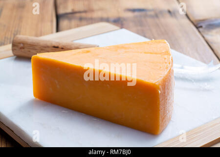Piece of bright yellow hard cheese cheddar, originating in the English village of Cheddar in Somerset close up - Stock Image