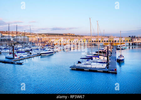 Brighton marina, Sussex, UK, a mixture of motor boats and sail boats floating on water, moured against lines of wooden quays behind are marina apartme - Stock Image