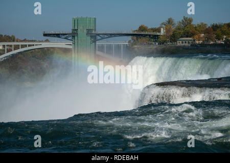 A rainbow over Niagara Falls with the Niagara Falls Observation Tower and Rainbow International Bridge in the background - Stock Image