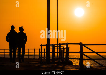 Aberystwyth, UK. 10th Apr, 2019. UK Weather: At the end of a day unbroken blue skies and warm spring sunshine, the sun sets  spectacularly behind the silhouettes of people walking along the promenade  in Aberystwyth on the Cardigan Bay coast of West Wales. Credit: keith morris/Alamy Live News - Stock Image