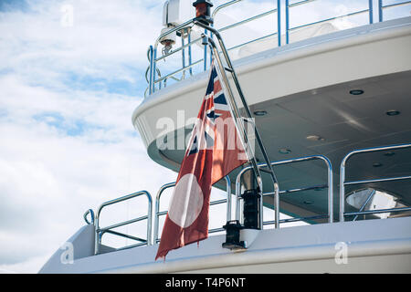 Part of a ship or vessel or yacht with the British flag against a blue sky. Concept of summer sea vacation or cruise. - Stock Image