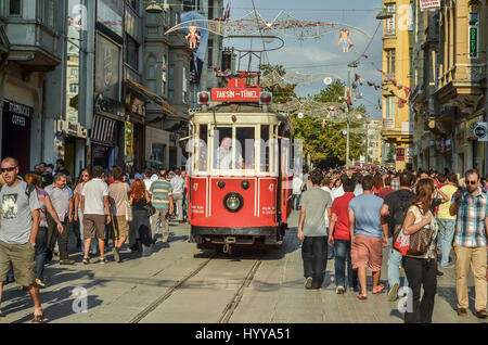Partial view of Istiklal street, with the historic streetcar approaching. - Stock Image