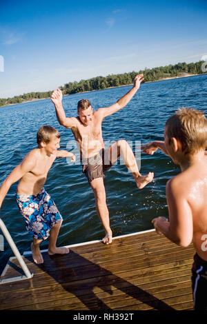 Father playing with sons at lake - Stock Image