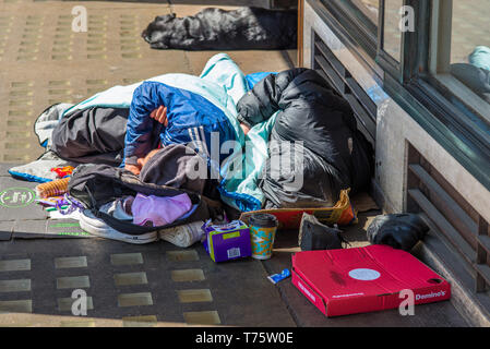 Two rough sleepers and their dog outside a store on Market square in Cambridge city centre, Cambridgeshire, England, UK. - Stock Image