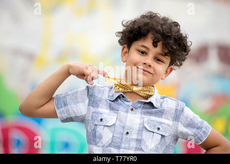 Proud young boy pointing to his gold colored bow tie with a friendly beaming smile in front of a colorful graffiti covered wall - Stock Image