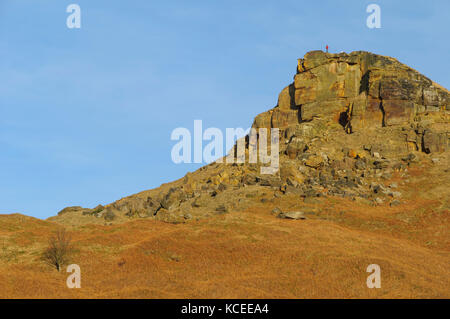 A lone figure standing on the peak of Roseberry Topping, a prominent and distinctive hill on the northern edge of - Stock Image