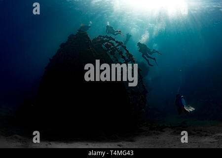 Underwater photographer of divers ascending over the shipwreck of Abu Ghoson, Egypt. - Stock Image