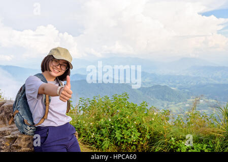 Tourist teens girl hiker wear cap and glasses with backpack poses thumb up smiling happily on high mountain at scenic - Stock Image