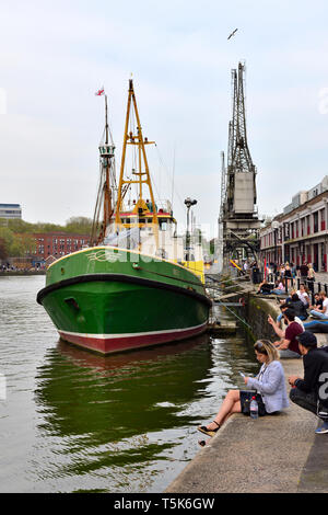 Bristol floating harbour, people sitting on Wapping Wharf quayside with supply vessel BEE of Bristol and historic Electric Cranes - Stock Image