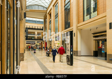 Interior of the Grand Arcade shopping centre with people walking past shop fronts, Cambridge, UK - Stock Image