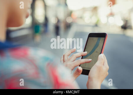 Close up woman using smart phone GPS on street - Stock Image