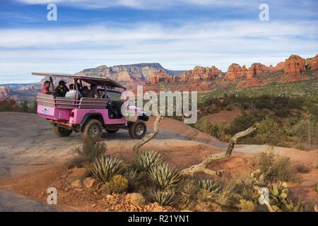 Pink Jeep Off Road Terrain Vehicle with Tourists on Broken Arrow Slick Rock and canyon landscape view near Sedona, Arizona - Stock Image