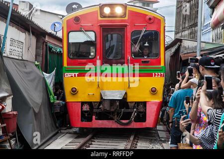 Maeklong, Thailand - August 29, 2018: Train crossing the Umbrella Pull Down Market on August 29, 2018 in Maeklong, Samut Songkhram, Thailand. - Stock Image