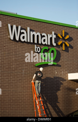 Contractor working on sign of new Walmart To Go concept convenience store under construction in Bentonville, AR, USA. - Stock Image