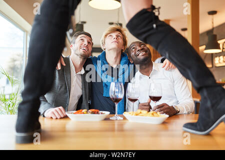 Friends in the restaurant at a striptease dinner as a bachelor party - Stock Image