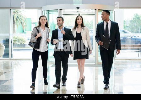 Business people talking while entering in hotel lobby - Stock Image