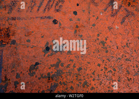 Gritty bright red texture on a rusted metal - Stock Image