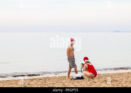 Benidorm, Costa Blanca, Spain, 25th December 2018. British tourists dress for the occasion on Christmas Day in this favourite getaway destination for Brits escaping the cold weather at home. Temperatures will be in the mid to high 20's Celsius today in this mediterranean hotspot. Woman in red swimming costume crouching on Levante beach with man in shorts standing nearby, both wearing santa hats. - Stock Image