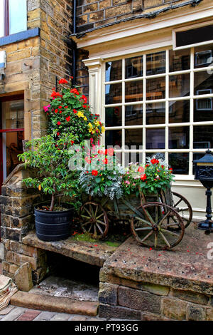 Aged Wooden Cartwith flowers in front of decorative window, Haworth, Keighley, West Yorkshire, England, UK - Stock Image