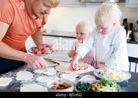 Father making pizza with sons - Stock Image
