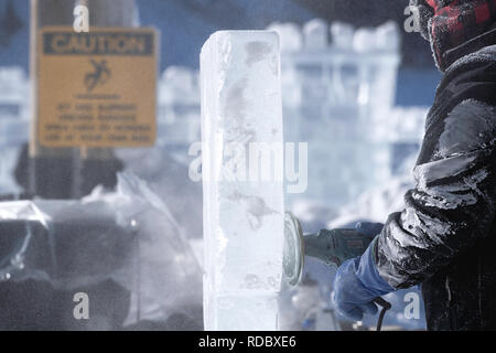Ice sculptor using an electric grinder to polish a sheet of ice  at the Lake Louise Ice Magic Festival in Banff National Park, Alberta Canada - Stock Image
