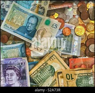 A collection of various bank notes and coins. Clearly visible are the Twenty Pound Sterling note, the new Five Pound Sterling note and the Ten U.S. Dollar Note/Bill. A picture for the Global Economy. - Stock Image