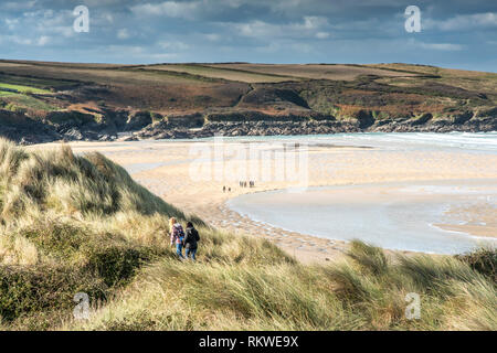 People walking through marram grass on the sand dune system overlooking Crantock Beach in Newquay in Cornwall. - Stock Image