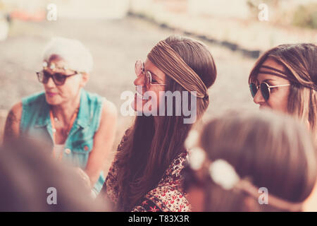 Hippy vintage concept with group of ladies together in friendship - brown colors filter and sun flowers period - alternative people in different love  - Stock Image