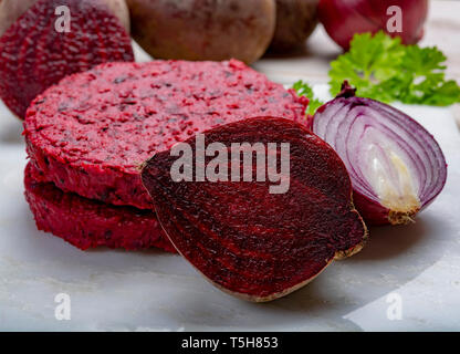 Healthy vegetarian food, raw round burgers made from red beetroot close up, good for vegans - Stock Image