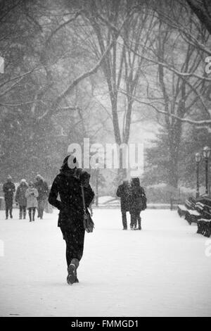 Woman walking in the snow - Stock Image