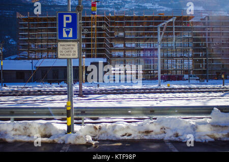 Parking metre at a car park in the snow in Sion, Switzerland. - Stock Image