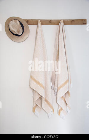 Towels hanging on hook on wall in bathroom - Stock Image