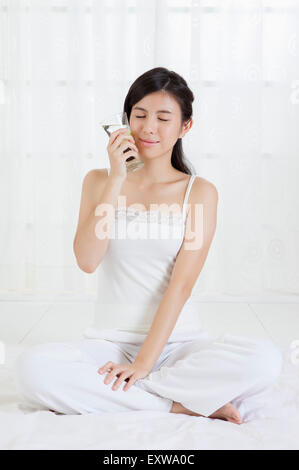 Young woman sitting and holding a carafe with eyes closed, - Stock Image