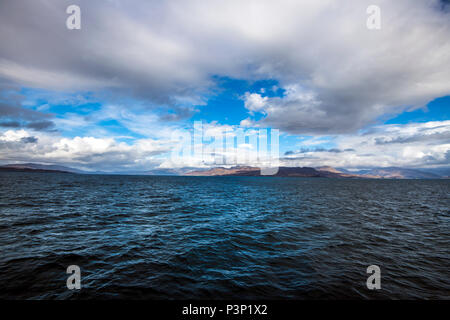 View of the sea channel between the Isle of Skye and the Scottish Mainland from the Armadale to Mallaig car ferry. - Stock Image