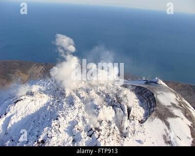 Steam rises from the snow-covered lava dome at the summit of Augustine Volcano on Augustine Island in the lower - Stock Image