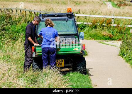 Two RSPB male and female man and woman staff at Bempton Cliffs working outdoors from an electric buggy. - Stock Image