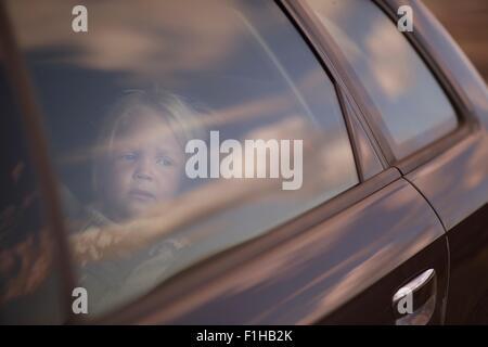 Boy looking through car window - Stock Image