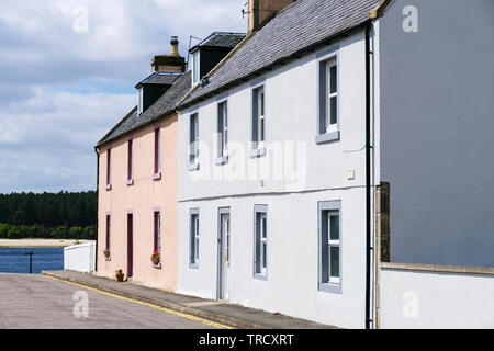 Traditional slate roof houses with front doors opening onto street leading to sea in village of Findhorn, Moray, Scotland, UK, Britain - Stock Image