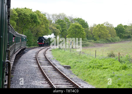 Locomotive 41313 on the Isle of Wight steam railway approaching carriages ready for coupling - Stock Image