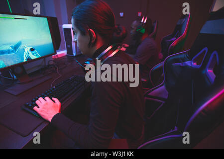 Concentrated Jewish guy with headset on neck sitting at table in dark room and playing computer network game - Stock Image