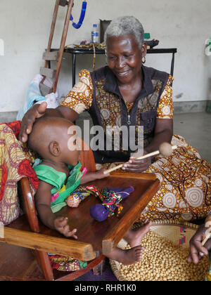 TANZANIA  -  Sean Sprague photo 2018  Physio-therapy workshop for children with special needs, Mabatini, Mwanza. 1-year-old baby girl suffers from cerebral palsy here assisted by Natalia Kadio, project coordinator. - Stock Image