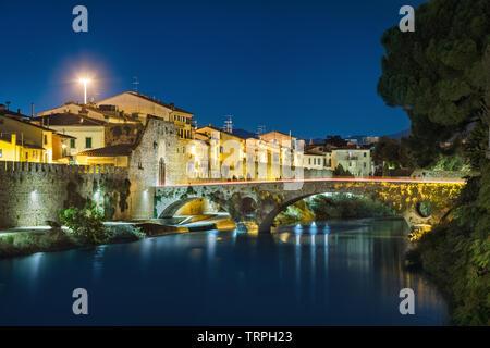 Medieval stone bridge and Mercatale Gate (Porta Mercatale) at dusk in Prato, Tuscany, Italy - Stock Image