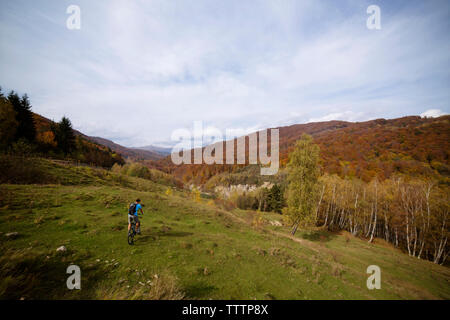 High angle view of man riding bicycle on Carpathian mountains against sky - Stock Image