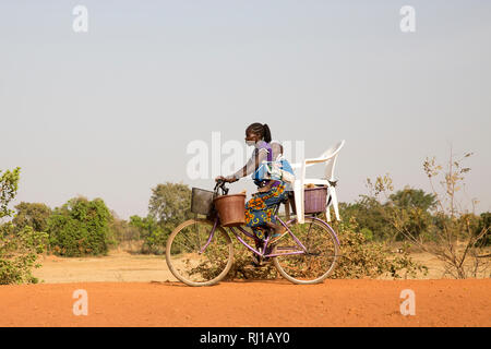 Samba village, Yako Province, Burkina Faso: A young woman carries her baby on her back and buckets and a chair on her bike. - Stock Image