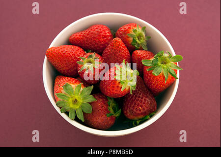 Generous bowl of overly ripe strawberries highly appreciated for their specific aroma, bright red color, juicy texture, and sweetness. - Stock Image