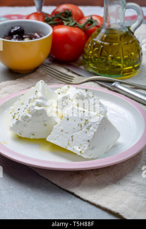 Fresh young soft white salted Feta cheese with olive oil on plate seasoned with dried oregano herb - Stock Image