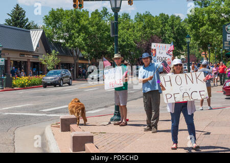 ESTES PARK, CO, USA-18 JULY 18:  A group of individuals with pro-peace and 'patriots for peace'  signs and American flags. - Stock Image