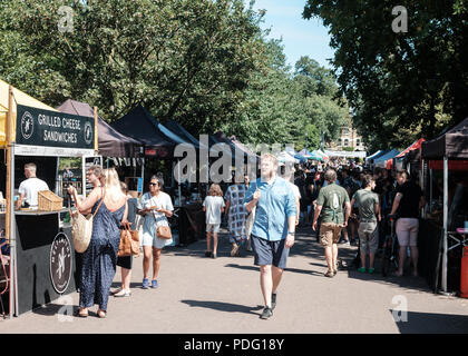 Shoppers and stalls in Victoria Park food market, held along the Nightwalk in Victoria Park,  East London, UK - Stock Image